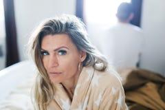 Koppla ihop att ha kris i s?ng Kvinna som sitter på sängs kant - som är tillbaka för att dra tillbaka royaltyfri fotografi