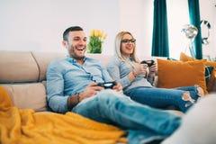 Koppla ihop att ha roligt och att skratta, medan spela videospel i modern vardagsrum arkivbild
