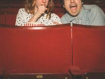 Koppla ihop att hålla ögonen på en läskig film i en filmbiograf Fotografering för Bildbyråer
