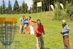 Koppla ihop att kasta frisbeedisketten på springtime parkerar Royaltyfri Bild