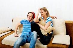 Koppla ihop att koppla av på soffan, den lyssnande musikkvinnan för mannen som kramar honom Arkivbild