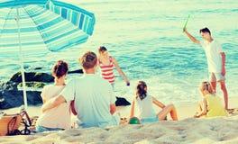 Koppla ihop att koppla av på stranden medan deras ungar som spelar aktiva lekar Royaltyfria Bilder