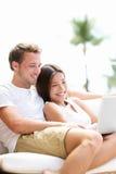 Koppla ihop att koppla av tillsammans i soffa med bärbar datorPC Royaltyfria Bilder