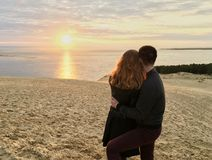 Koppla ihop att krama, medan hålla ögonen på solnedgångsikten från dyn av Pyla som är högst i Europa Frankrike den sandiga strand arkivfoto