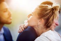 Koppla ihop att krama medan kvinnan som blåser en kyss till en annan man Royaltyfri Bild