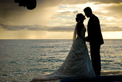 Koppla ihop att kyssa efter ett bröllop på stranden Royaltyfri Foto
