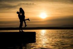 Koppla ihop att kyssa på stranden med en härlig solnedgång Arkivfoto
