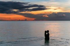 Koppla ihop att kyssa på stranden med en härlig solnedgång i bakgrund royaltyfri bild