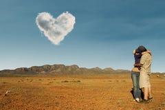 Koppla ihop att kyssa på den australiska öknen under förälskelsemolnet Arkivfoton