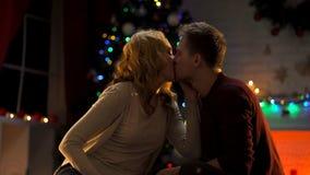 Koppla ihop att kyssa passionately under julgranen, ferieatmosfär, förälskelse royaltyfri foto
