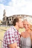 Koppla ihop att kyssa som är förälskat i Rome vid Colosseumen Arkivfoton