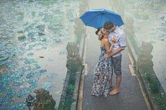 Koppla ihop att kyssa under regnet på deras första datum Royaltyfri Foto