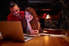 Koppla ihop att lägga på golv och att använda bärbar datordatoren hemma royaltyfria foton