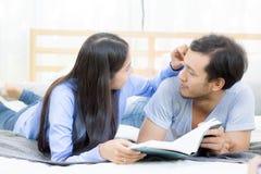 Koppla ihop att läsa en bok tillsammans i sovrum på morgonen med lyckligt Royaltyfri Fotografi