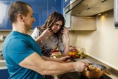 Koppla ihop att laga mat hemma, frun som inte imponeras med cookin för make` s Royaltyfri Bild