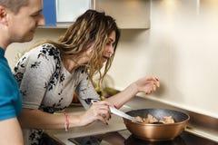 Koppla ihop att laga mat hemma, frun som inte imponeras med cookin för make` s Arkivbilder