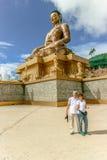 Koppla ihop att le nära den jätte- BuddhaDordenma statyn med den blåa himlen och fördunklar bakgrund, Thimphu, Bhutan Arkivbilder