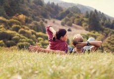 Koppla ihop att ligga i grönt gräs på skogkullen arkivfoto