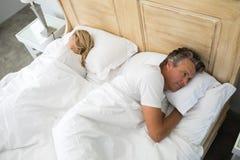 Koppla ihop att ligga på säng som har after ett argument Arkivbilder