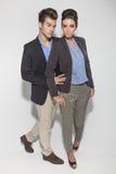 Koppla ihop att posera på ljus - grå studiobakgrund Royaltyfria Foton
