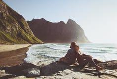 Koppla ihop att resa tillsammans att koppla av på den Kvalvika stranden i Norge arkivbilder