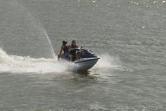 Koppla ihop att rida en stråle skidar i en sjö arkivfoto
