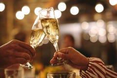 Koppla ihop att rosta champagneexponeringsglas på partiet arkivfoton