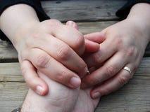 Koppla ihop att rymma händer på en trätabell arkivfoton