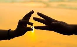 Koppla ihop att sätta förlovningsringen in i cirkelfingret av annat romantisk solnedgång på stranden royaltyfria bilder