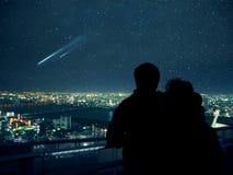Koppla ihop att se över Osaka natthorisont och fallande stjärnor royaltyfri fotografi