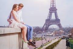 Koppla ihop att sitta nära Eiffeltorn i Paris, bröllopsresa i Europa royaltyfri fotografi