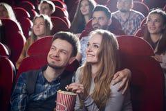 Koppla ihop att sitta tillsammans i bion som håller ögonen på komedi arkivbild