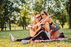 Koppla ihop att sjunga och att spela gitarren på en picknick Royaltyfri Bild