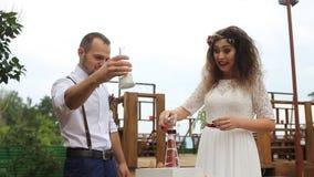 Koppla ihop att skratta på bakgrunden av bröllopgarneringarna Sandblandningen arkivfilmer