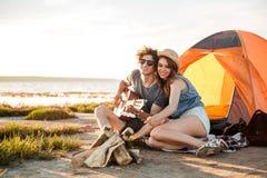 Koppla ihop att spela gitarren och att steka marshmallower på brasa tillsammans fotografering för bildbyråer
