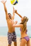Koppla ihop att spela med en boll på stranden royaltyfri fotografi