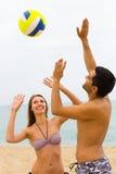 Koppla ihop att spela med en boll på stranden Arkivfoto