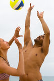 Koppla ihop att spela med en boll på stranden Fotografering för Bildbyråer