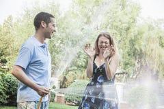 Koppla ihop att spela med en trädgårds- slang och att bespruta sig utanför i trädgården Royaltyfri Bild