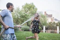 Koppla ihop att spela med en trädgårds- slang och att bespruta sig utanför i trädgården Royaltyfria Foton
