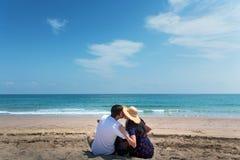 Koppla ihop att spendera tid p? stranden med en gitarr royaltyfri foto