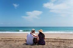 Koppla ihop att spendera tid p? stranden med en gitarr royaltyfria bilder