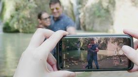 Koppla ihop att ta bilder med en telefon nära en vattenfall lager videofilmer