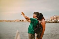 Koppla ihop att ta fotoet med en smart telefon på kanten av havet Arkivfoto