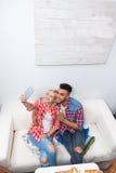 Koppla ihop att ta innehavet för selfiebildflickan den smarta soffan för telefonsammanträdecoffee shop den bästa vinkeln royaltyfri fotografi