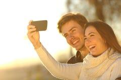 Koppla ihop att ta selfiefotoet med en smart telefon på solnedgången Arkivfoton
