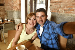 Koppla ihop att ta selfiefotoet med mobiltelefonen på att le för coffee shop som är lyckligt i romanskt förälskelsebegrepp Royaltyfri Foto