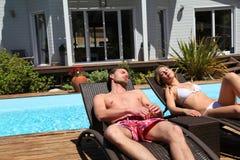 Koppla ihop att ta solen i långa stolar i sommar Arkivfoto