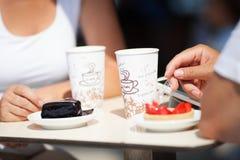 Koppla ihop att tycka om kaffe och kakan på en kafeteria Royaltyfri Fotografi
