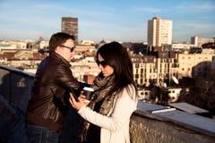 Koppla ihop att tycka om på taket, flickadrinkkaffe och användasmartphonen Arkivbild